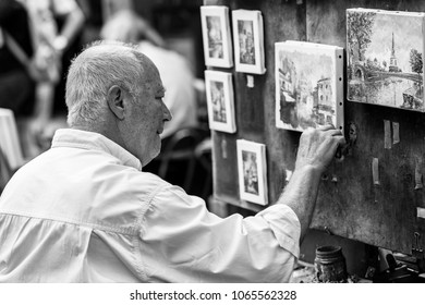 Paris, France - July 06, 2017: The painter works at the open air artist market at the Tertre Square (Place du Tertre) in the Montmartre district. (Black and white)