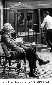 Paris, France - July 06, 2017: A traditional restaurant in Paris, in the Butte Montmartre.  Old aged man sits on the terrace of the restaurant with coffee and a cigarette. Black and white.