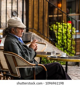 Paris, France - July 06, 2017: A traditional restaurant in Paris, in the Butte Montmartre.  Old aged man sits on the terrace of the restaurant with coffee and a cigarette.