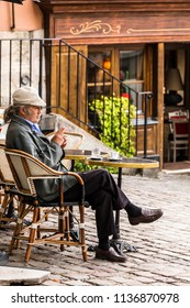 Paris, France - July 06, 2017: A traditional restaurant in Paris, in the Butte Montmartre.  Senior man sits on the terrace of the restaurant with coffee and a cigarette.