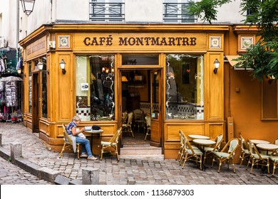 Paris, France - July 06, 2017: The charming Cafe Montmartre on Montmartre hill. Woman sitting at the table. Montmartre is one of the most visited landmarks in Paris.