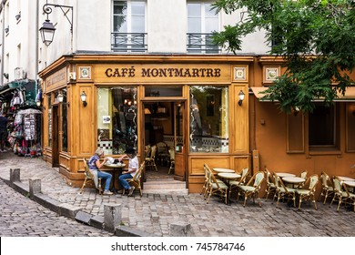 Paris, France - July 06, 2017: The charming Cafe Montmartre on Montmartre hill. Senior couple sitting at table and drinking coffee.