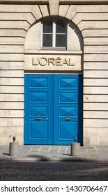 Paris, France - July 06, 2018: Bright blue door with decorative handles as the entrance to the Loreal brand store in Paris