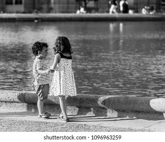 Paris, France - July 07, 2017: Little friends girl and boy playing in the Luxembourg Gardens (Jardin du Luxembourg), one of largest public park in Paris, in the summer at sunset. Black and white