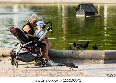 Paris, France - July 07, 2017: Grandmother and grandson feed the pigeons in the Luxembourg Gardens (Jardin du Luxembourg), one of largest public park in Paris, in summer at sunset.