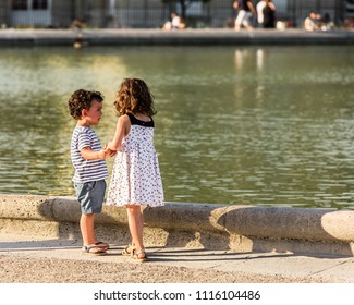 Paris, France - July 07, 2017: Little friends girl and boy playing in the Luxembourg Gardens (Jardin du Luxembourg), one of largest public park in Paris, in the summer at sunset.