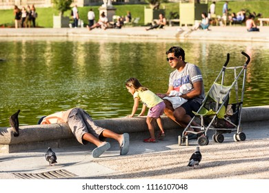 Paris, France - July 07, 2017: Dad with his children feed the birds in the Luxembourg Gardens (Jardin du Luxembourg), one of largest public park in Paris, in the summer at sunset.