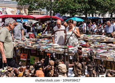 Paris, France - July 09, 2017: People choosing rare and used books, wooden masks and figures of African culture at the historic flea Aligre Market (Marche d'Aligre) in the Bastille district.