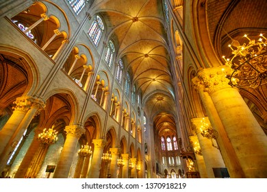 PARIS, FRANCE - JULY 1, 2017: interior colonnade panorama of Notre Dame Gothic cathedral left side nave. Candelabrum ceiling chandeliers on top roof nave.