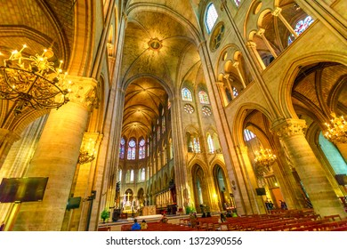 PARIS, FRANCE - JULY 1, 2017: interior colonnade panorama of Notre Dame Gothic cathedral left side nave and Candelabrum chandeliers on top of the ceiling.