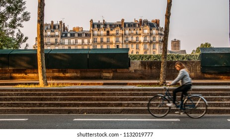 Paris, France - July 10, 2018: Girl on bike on the streets of Paris's 5th disrict along the Seine River. First days of summer in the city