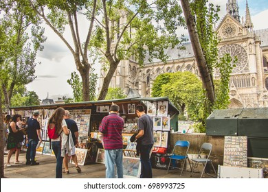 PARIS, FRANCE - July 11, 2017 : Traditional Bouquiniste booth on the edge of the Seine in front of the Notre-Dame cathedral. The Bouquinistes sell used and antique books as well as souvenirs.