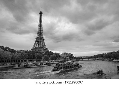 Paris, France - July 18, 2019: Black and white photograph of tourist boats navigating the River Seine and Eiffel Tower in Paris, France