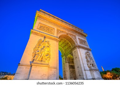 Paris, France - July 2, 2017: Night view of Arch of Triumph at the center of the Place Charles de Gaulle. Bottom view of popular landmark at blue hour with illuminated Eiffel Tower.