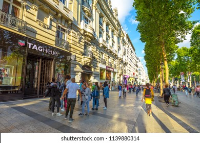 Paris, France - July 2, 2017: tourists walk on the most famous avenue in Paris, the Champs Elysees, known for luxury and shopping that starts from Place de La Concorde to Place Charles de Gaulle.