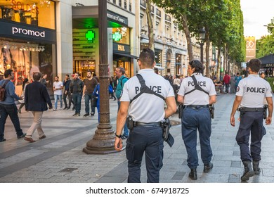 PARIS, FRANCE - JULY 2, 2017: policemen on the road, keeping security after recent terrorist attacks in Paris. Patrolling the Avenue des Champs Elysees from the Place Charles de Gaulle, Triumphal Arch
