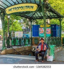 PARIS, FRANCE - JULY 2, 2018: An unidentified street musician at one of the old-style entrances to the Abbesses Metro station.