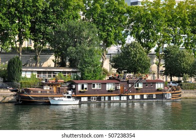 PARIS, FRANCE - JULY 2: Floating house ship on the river Seine near the Swan Island in Paris.