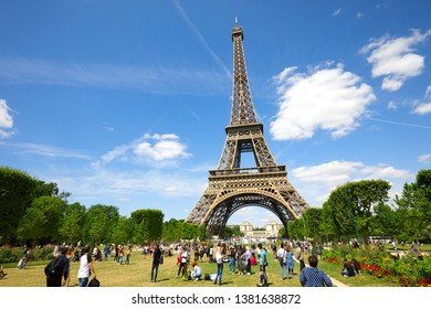 PARIS, FRANCE - JULY 21, 2017: Eiffel Tower in Paris and green field of Mars meadow with people and tourists in a sunny summer day, blue sky