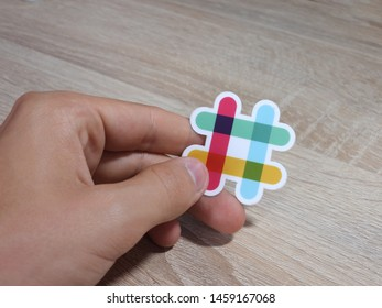 Paris, France - July 23, 2019 : Slack logo sticker held by a hand. Background is a wooden table. Slack is an American set of team collaboration software tools and online service.