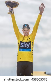 PARIS, FRANCE - JULY 24, 2016 : The road racing cyclist Christopher Froome winner of Tour de France 2016, wearing the leader's yellow jersey on the fist step of the podium celebrates his victory.
