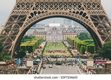 Paris, France July 24, 2017: Eiffel Tower close-up of a road with cars and buses traffic from a transporter, passage under an arch, a square for tourists. A lot of people walking on foot.