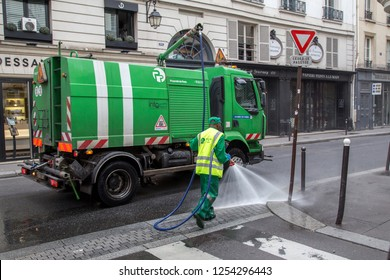 Paris, France - July 24, 2017: A sweeper car and a worker cleaning the streets