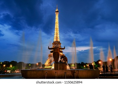 PARIS, FRANCE- JULY 27, 2018: Trocadero park sculpture of a bull in front of the illuminated Eiffel tower in Paris. Tourists on the right taking photos of the attraction.