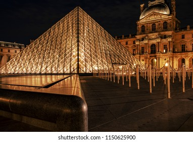 PARIS, FRANCE- JULY 27, 2018: Night photo of the illuminated louvre museum with the surrounding historic buildings.