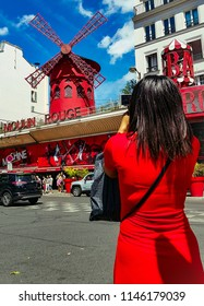 PARIS, FRANCE - JULY 28, 2018: Rear view of woman in red dress photographing the famous Moulin Rouge facade in Paris