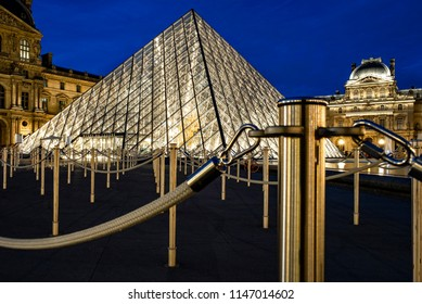 PARIS, FRANCE- JULY 28, 2018: Entrance of the Louvre Museum with its golden shining barriers.
