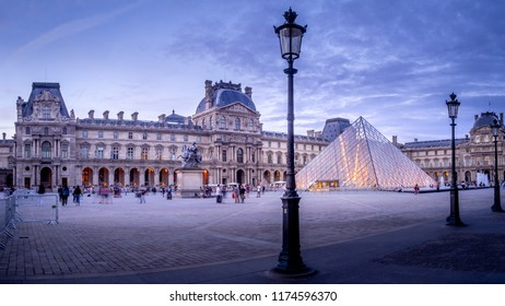 Paris, France - July 28, 2018: Outside the Louvre Museum in Paris, France in the evening. Tourists and people are visible in the courtyard where the pyramid entrance is located.