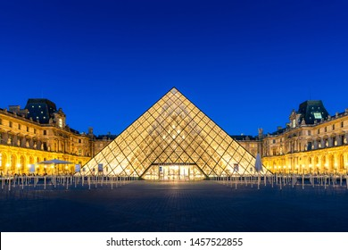 Paris, France - July 4, 2019: View of famous Louvre Museum with Louvre Pyramid at night. Louvre Museum is one of the largest and most visited museums worldwide in Paris, France.