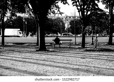 Paris, France - July 5, 2019: Man sitting on a park bench amidst trees and on a street in Paris.