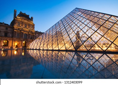 PARIS, FRANCE - JULY 6: The Louvre Pyramid at dusk during the Michelangelo Pistoletto Exhibition on July 6, 2013 in Paris. The Pyramid is the main entrance to the Louvre Museum. Completed in 1989.
