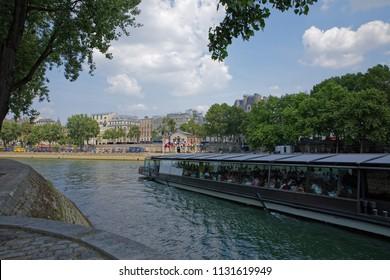 Paris, France - July 7, 2018: Tourist boat  over river Seine in Paris