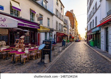 Paris, France - July 7, 2018: Street with tables of cafe in quarter Montmartre in Paris, France. Cozy cityscape of Paris. Architecture and landmarks of Paris.