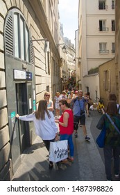 Paris, France - July 7, 2018: A narrow street in the Latin Quarter of Paris on the left bank of the Seine with many tourists walking and shopping
