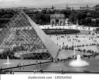 PARIS, FRANCE - JULY 9, 2006: Square before Louvre with pyramid and fountains in Paris, France on July 9, 2006.