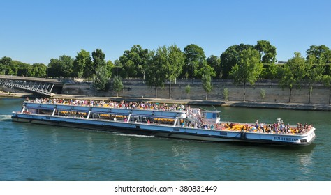 Paris, France - July 9, 2015: Tourists embark on cruise boat on river Seine by Orsay Museum in Paris, France
