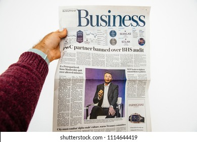 PARIS, FRANCE - JUN 13, 2018: Man holding The Daily Telegraph with portrait of Elon Musk CEO of tesla saying he is cutting 9 percent of jobs