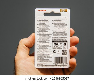 Paris, France - Jun 15, 2018: Man hand holding in hand a new Toshiba 64 gb microSDXC UHS-i Card with adapter rear view