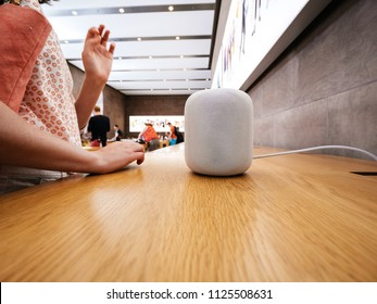 PARIS, FRANCE - JUN 30, 2018: Side view of woman testing deciding to buy in Apple Store the latest Apple Computers HomePod smart speaker developed by the computer firm