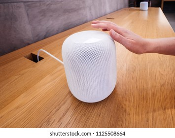 PARIS, FRANCE - JUN 30, 2018: Woman ttouching in Apple Store the latest Apple Computers HomePod smart speaker developed by the computer firm push button volume