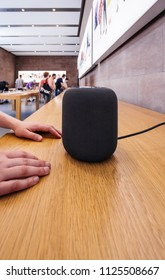 PARIS, FRANCE - JUN 30, 2018: Woman admiring in Apple Store the latest Apple Computers HomePod smart speaker developed by the computer firm