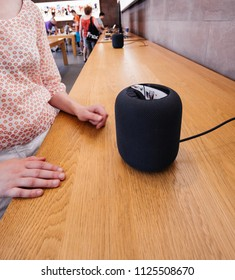 PARIS, FRANCE - JUN 30, 2018: Apple Store the latest Apple Computers HomePod smart speaker developed by the computer firm - woman deciding to buy or not
