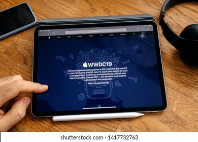 Paris, France - Jun 6, 2019: Man reading on Apple iPad Pro tablet about latest announcement of at Apple Worldwide Developers Conference WWDC - showing the splash page of Apple US website