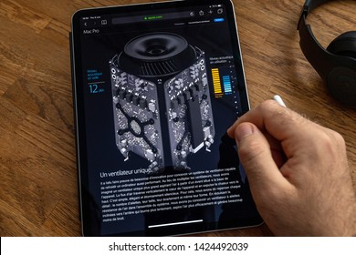 Paris, France - Jun 6, 2019: Man reading on Apple iPad Pro tablet about powerful professional workstation computer Mac Pro with new silent 12 dBA