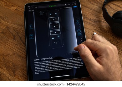 Paris, France - Jun 6, 2019: Man reading on Apple iPad Pro tablet about powerful professional workstation computer Mac Pro with other E S connexion thunderbolt 2