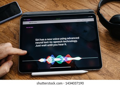 Paris, France - Jun 6, 2019: Man reading on Apple iPad Pro tablet about latest announcement of at Apple Worldwide Developers Conference (WWDC) - showing the new Siri video